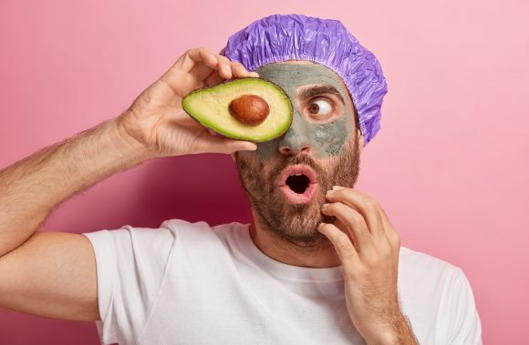 Horizontal shot of surprised European man keeps mouth opened from wonder, covers eye with slice of avocado, dressed in casual wear, shower cap, isolated over pink background. Spa and beauty concept