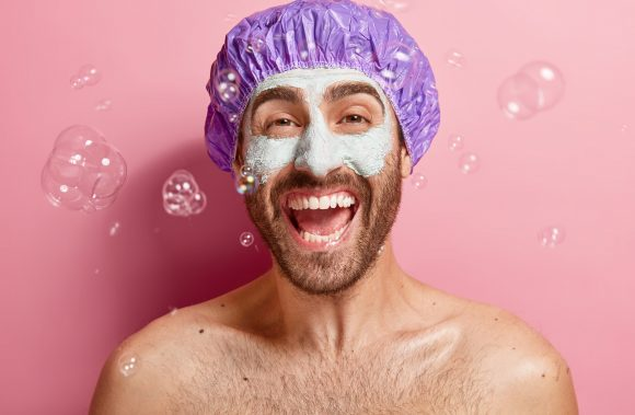Indoor shot of emotive satisfied man with clay mask, enjoys taking shower and facial treatment, wears bathcap, soap bubbles flying around, washes body, poses topless. Cleanliness, hygiene concept
